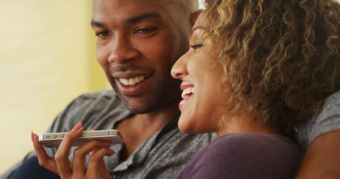 couple talking into smartphone in speaker mode