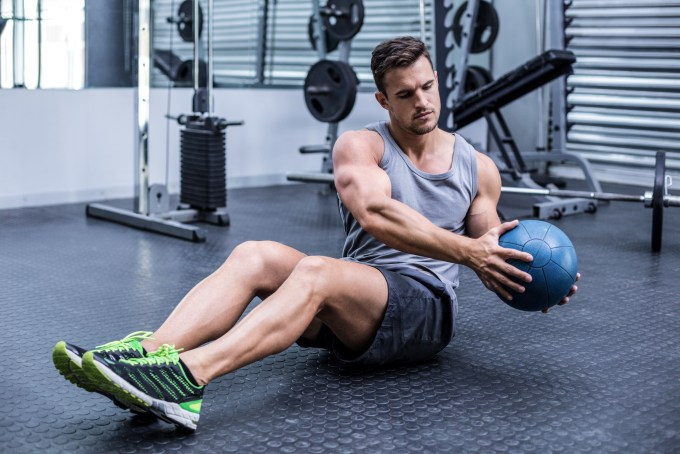 man exercising at gym with medicine ball