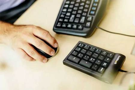 worker using ergonomic mouse, keyboard and numeric keypad