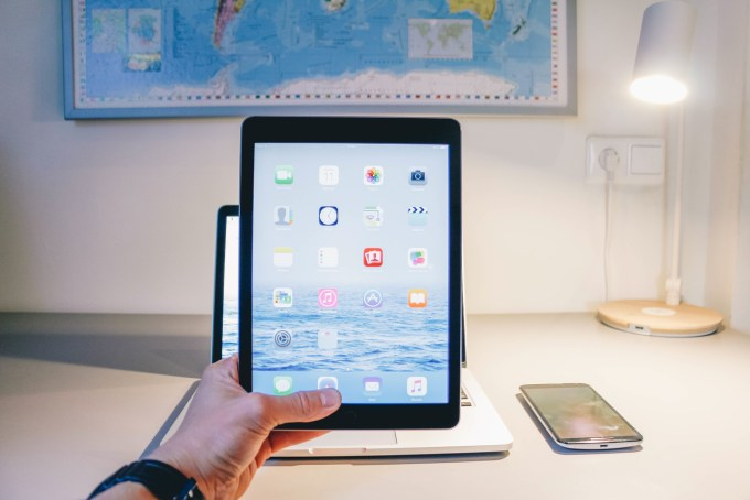 Man holding up a tablet touch screen iPad electronic device