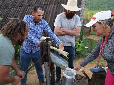 Learning from the locals about how to extract juice from sugar cane
