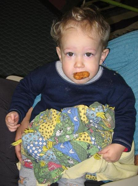 Nickalus sucking on a chicken nugget while clutching his blanket