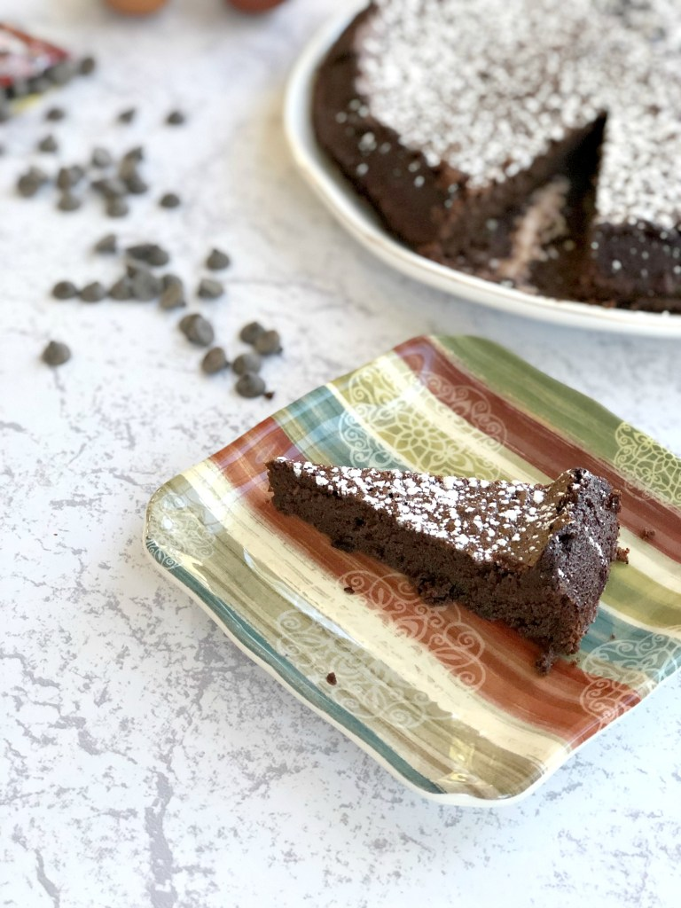 Slice of Flourless Chocolate Torte for Passover with full cake in background