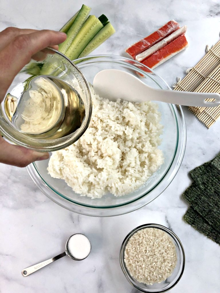 Adding vinegar sugar mixture to sushi rice