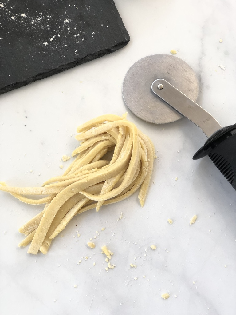 A pizza cutter with cut pasta dough strips
