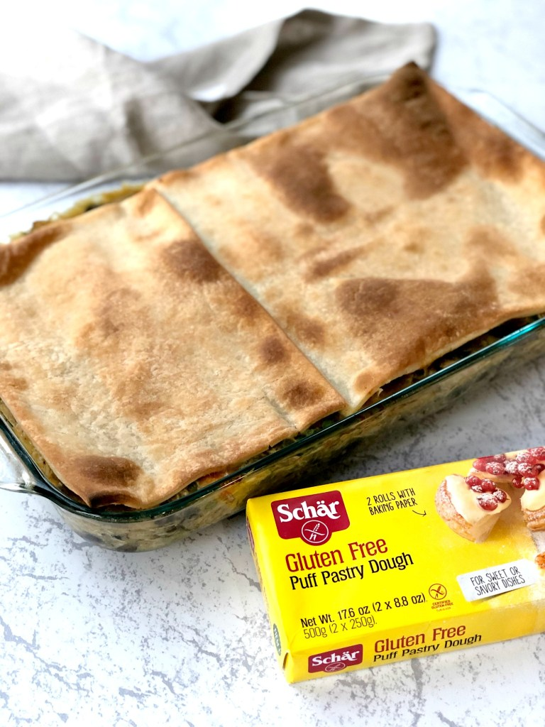 Gluten-Free puff pastry covering chicken pot pie casserole with picture of box of Schar gluten-free puff pastry dough