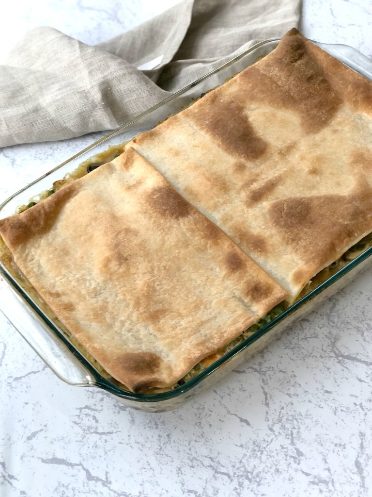 Gluten-free chicken pot pie cooked in casserole dish topped with browned puff pastry dough