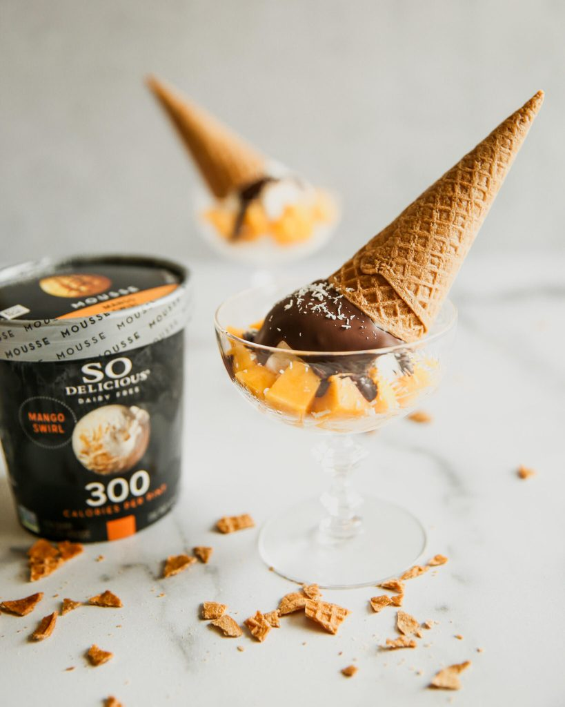 So Delicious mango frozen mousse carton with sundae scoop of ice cream in a bowl with mangos, shreds of coconut, magic shell topping and ice cream cone