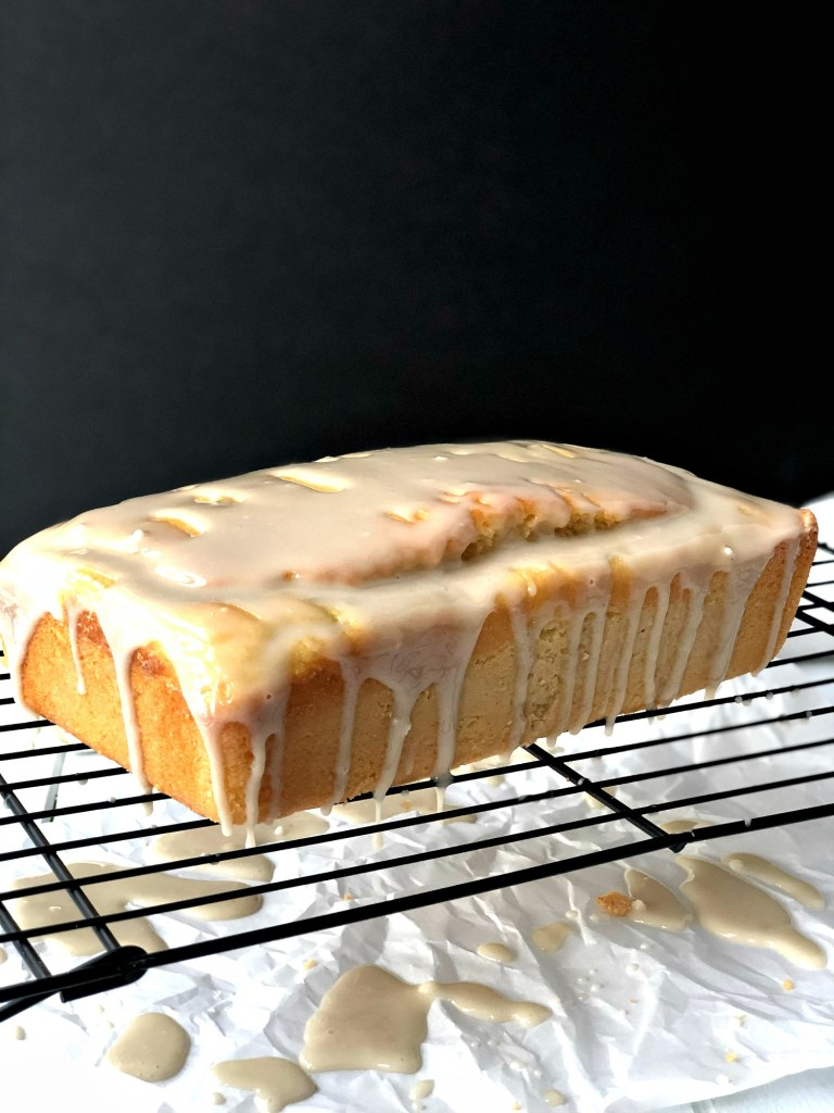 Gluten-Free lemon vanilla pound cake with icing dripping off sides