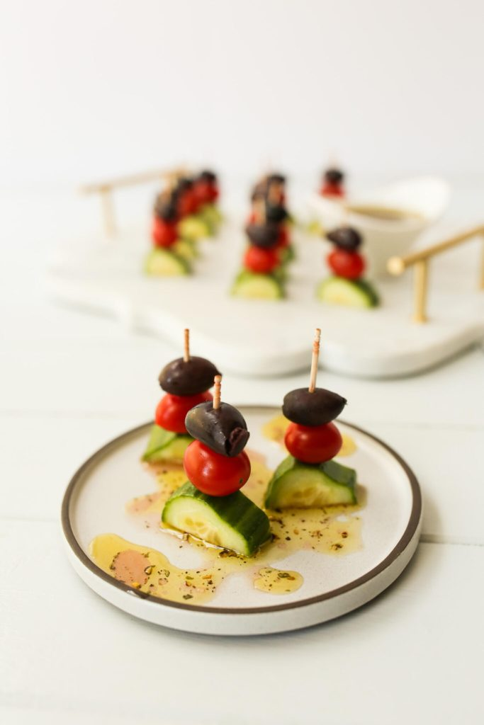 Greek Salad Kabobs on a plate with dressing