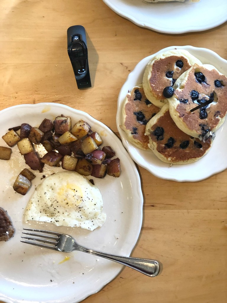Overhead shot of pancakes and eggs and potatoes at the original pancake house with Nima SEnsor testing for gluten
