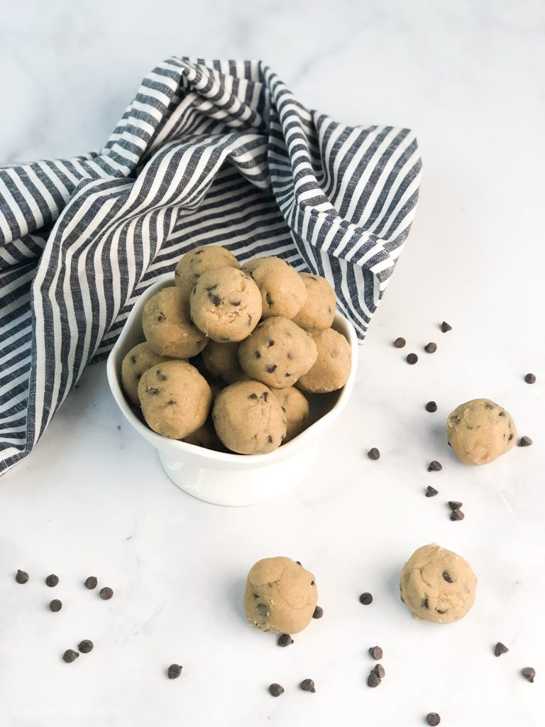display of several gluten-free chocolate chip cookie dough balls in a bowl and on a table