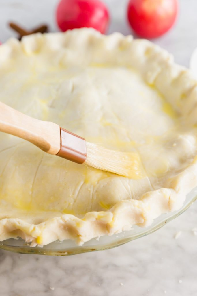 Gluten-free apple pie being brushed with an egg wash topping
