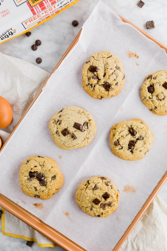 Gluten-free chocolate chunk cookie fully cooked and sitting on a baking sheet