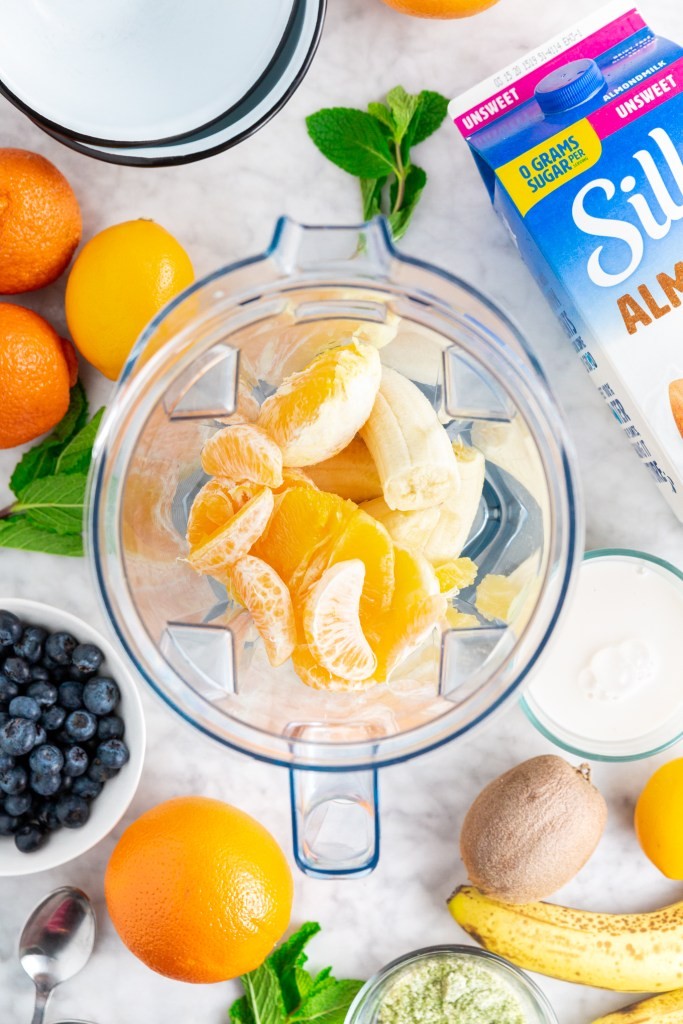 All the ingredients combined inside the blender to make the Dairy-Free Citrus Mint Smoothie Bowl