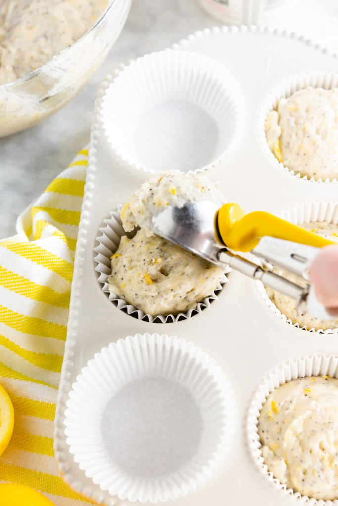 Picture of scooping gluten-free lemon poppy seed muffins batter into muffin tins