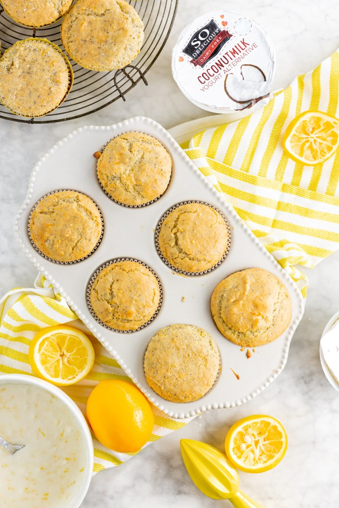 Second picture of cooked gluten-free lemon poppy seed muffins with lemons and So Delicious coconutmilk yogurt alternative in picture.