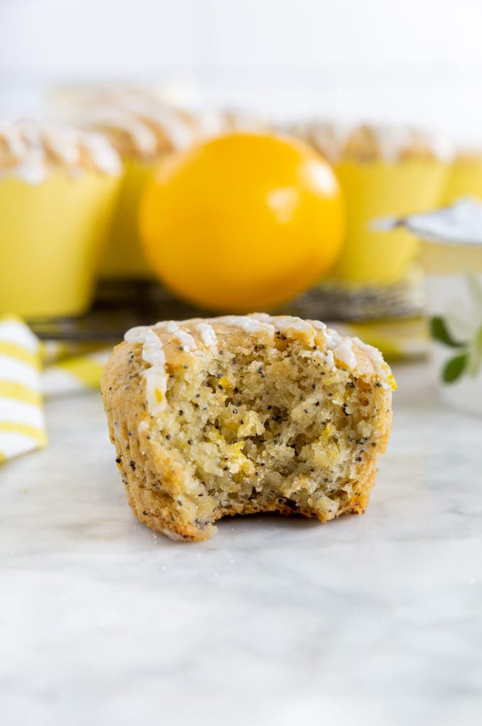 Picture of someone taking a bite out of the gluten-free lemon poppy seed muffin. It's moist!