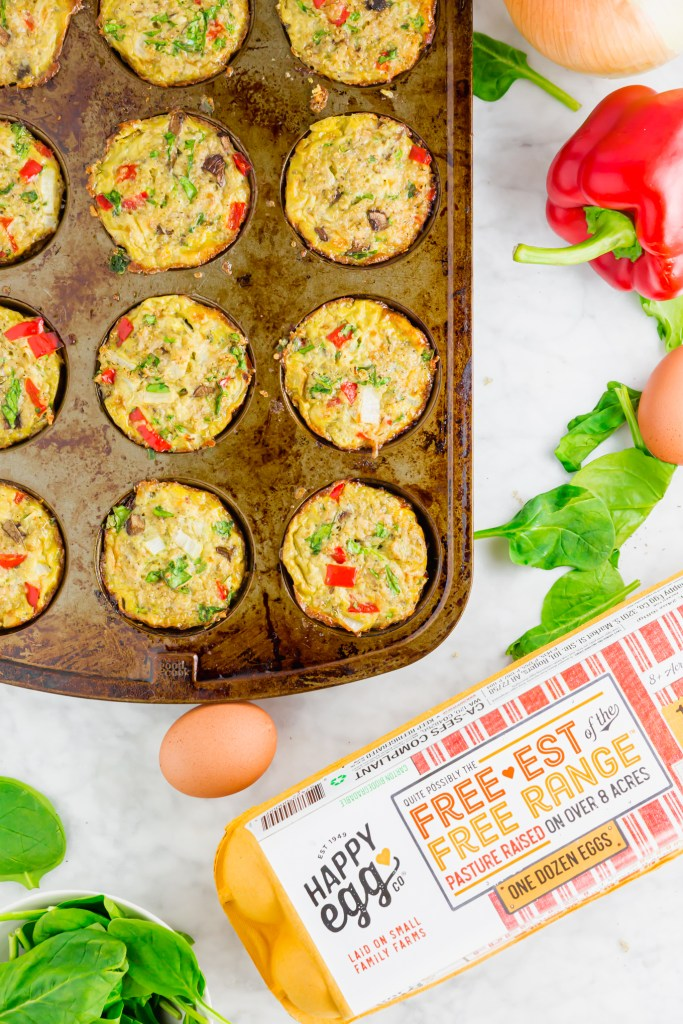 Another overhead image of cooked High-Protein Vegetable Quinoa Egg Muffins with Happy Egg carton in picture