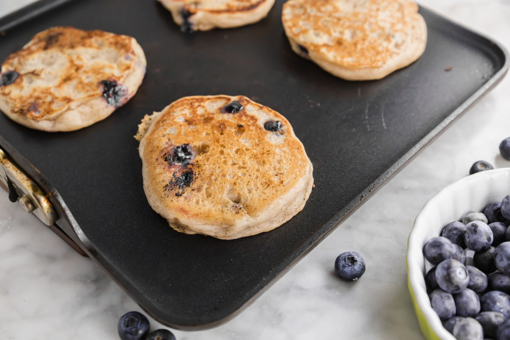 gluten-free blueberry yogurt pancakes on the griddle cooking