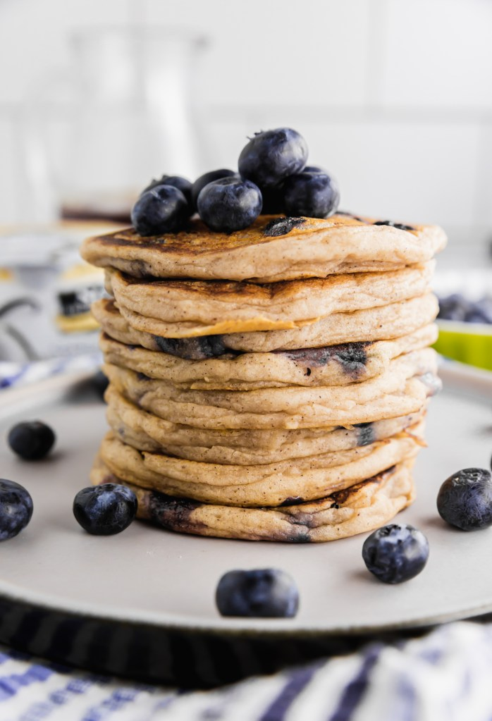 Beautiful stack of gluten-free pancakes. Pancakes are topped with additional fresh blueberries.