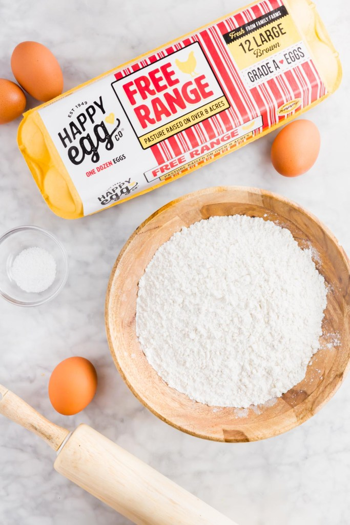 Picture of Happy Egg Co egg carton with flour and eggs surrounding it.