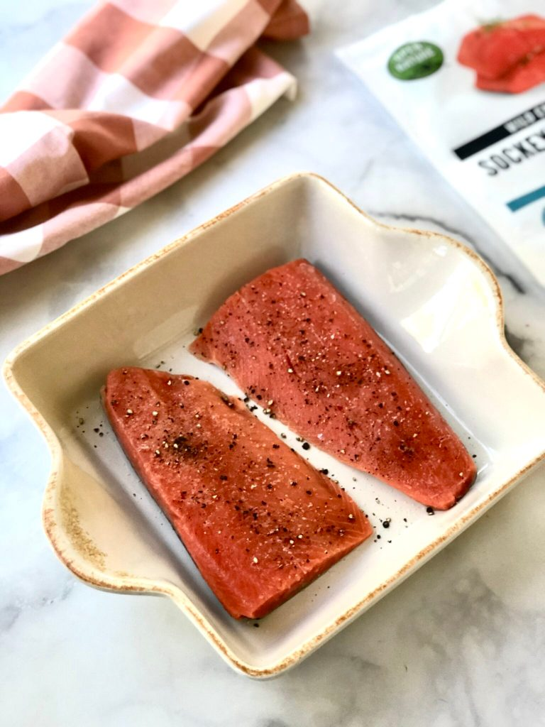 Picture of two seasoned wild salmon fillets in a baking dish.
