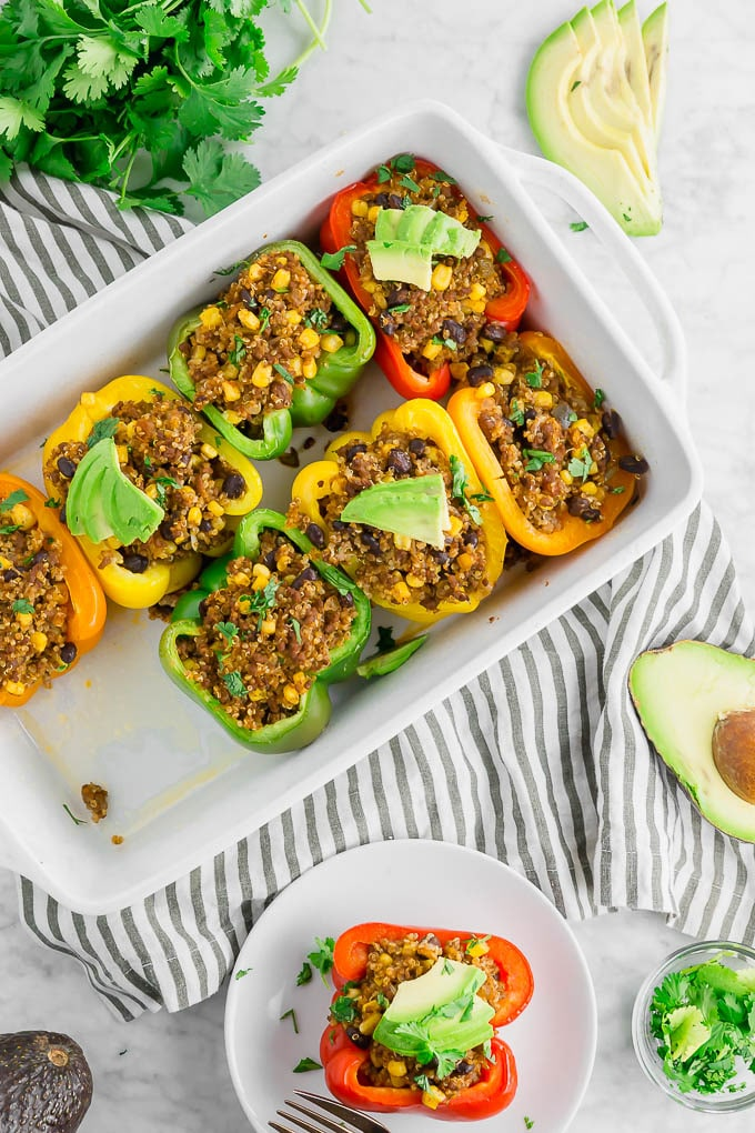 Picture of beef, quinoa, black bean and corn-stuffed bell peppers inside a casserole dish. Recipe by A Dash of Megnut.