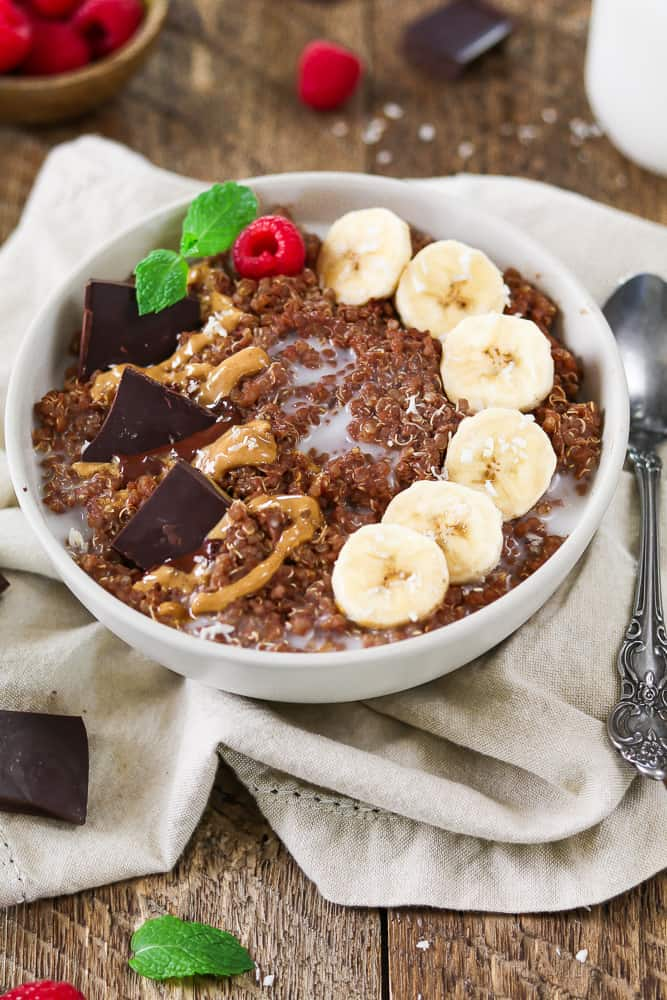Picture of bowl with chocolate quinoa, bananas, peanut butter drizzle. Recipe by Vegan Huggs.