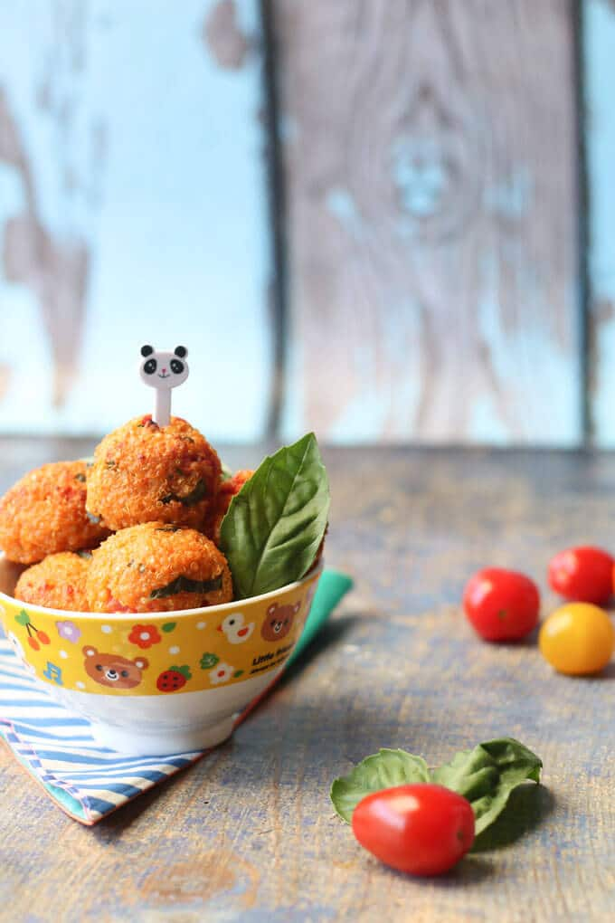 Bowl of cheese and tomato quinoa balls with a toothpick in the center of one by Healthy Little Foods.