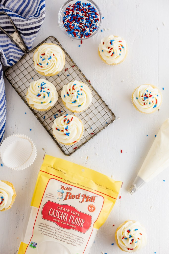Overhead picture of multiple frosted cassava flour cupcakes with sprinkles, a piping bag, and Bob's Red Mill Cassava Flour bag showing.