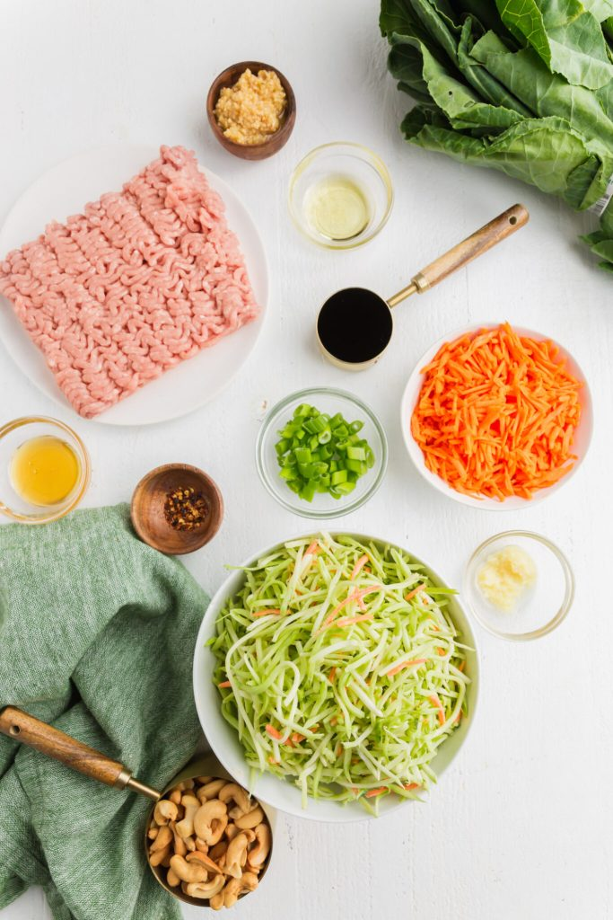overhead picture of ingredients needed for egg roll filling including ground chicken, broccoli slaw, carrots and seasonings