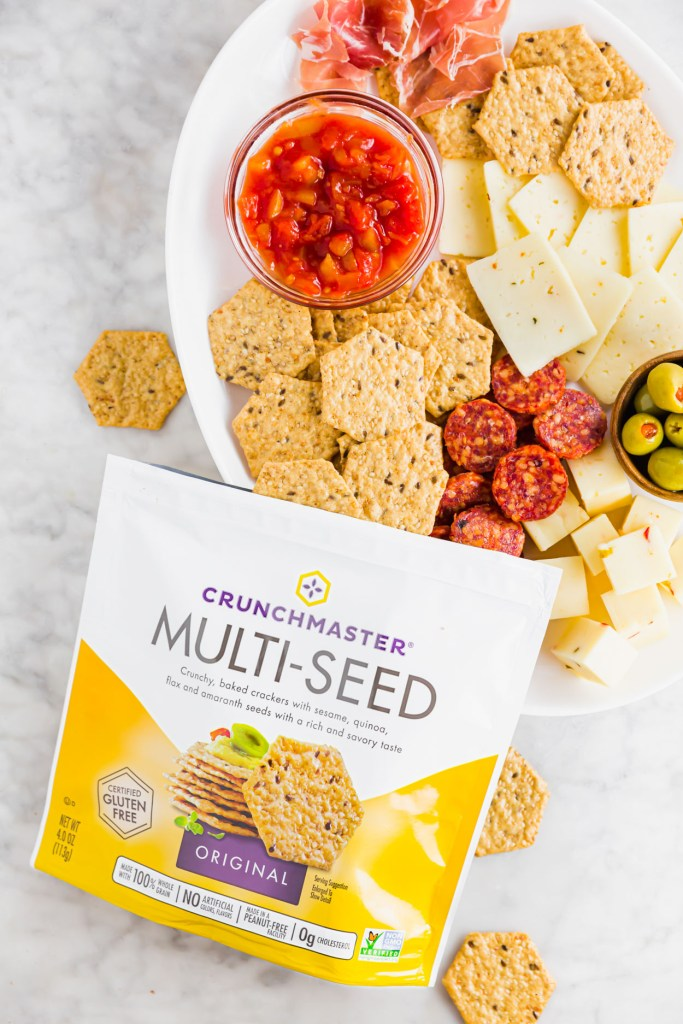 Oval snack board with crackers, cheese and deli meats as well as up close picture of Crunchmaster  multi-seed crackers