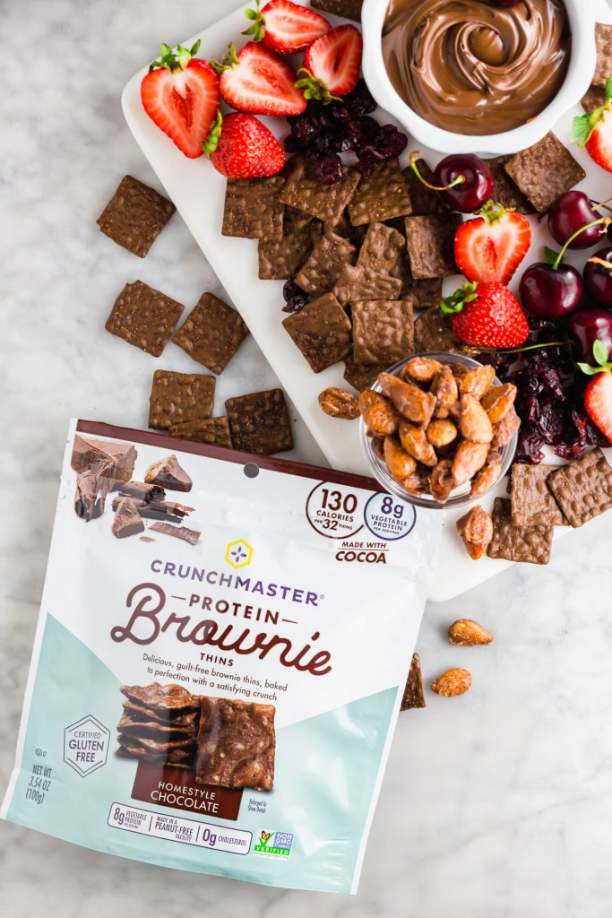 Overhead image of chocolate-themed snack board and picture of Crunchmaster protein brown thin crackers