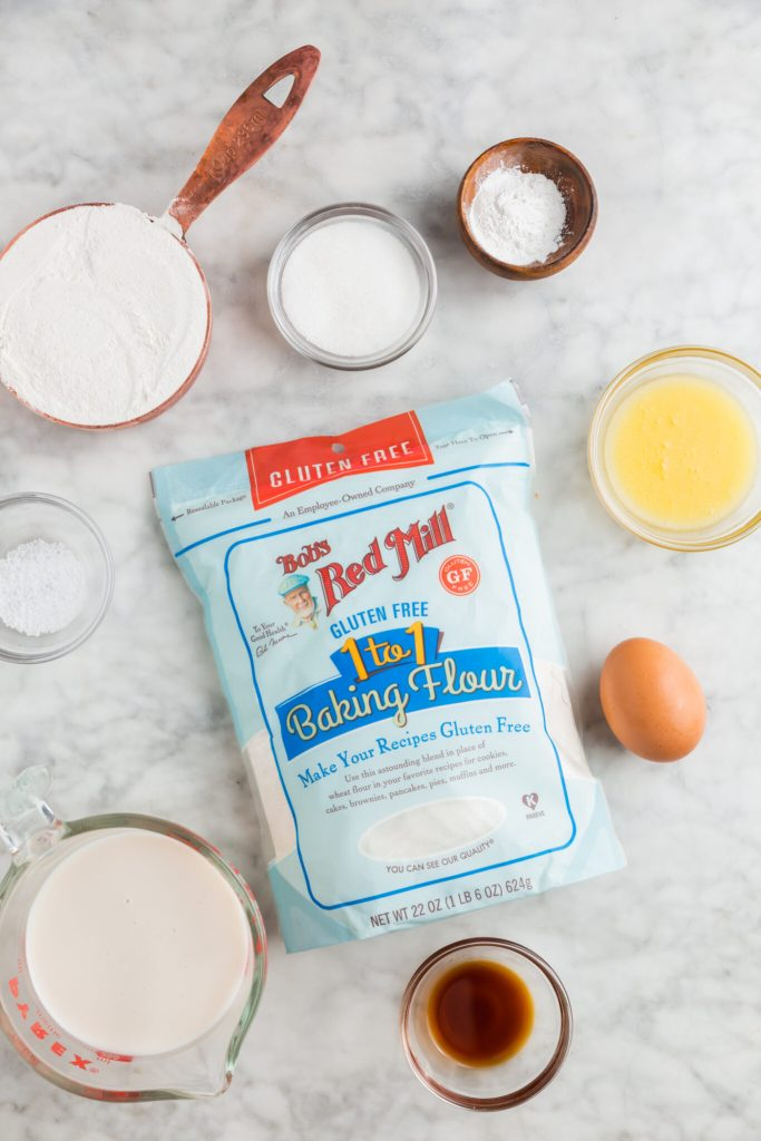 Bob's Red Mill flour laying on countertop and surrounded by the ingredients needed to make the no-fail gluten-free pancakes
