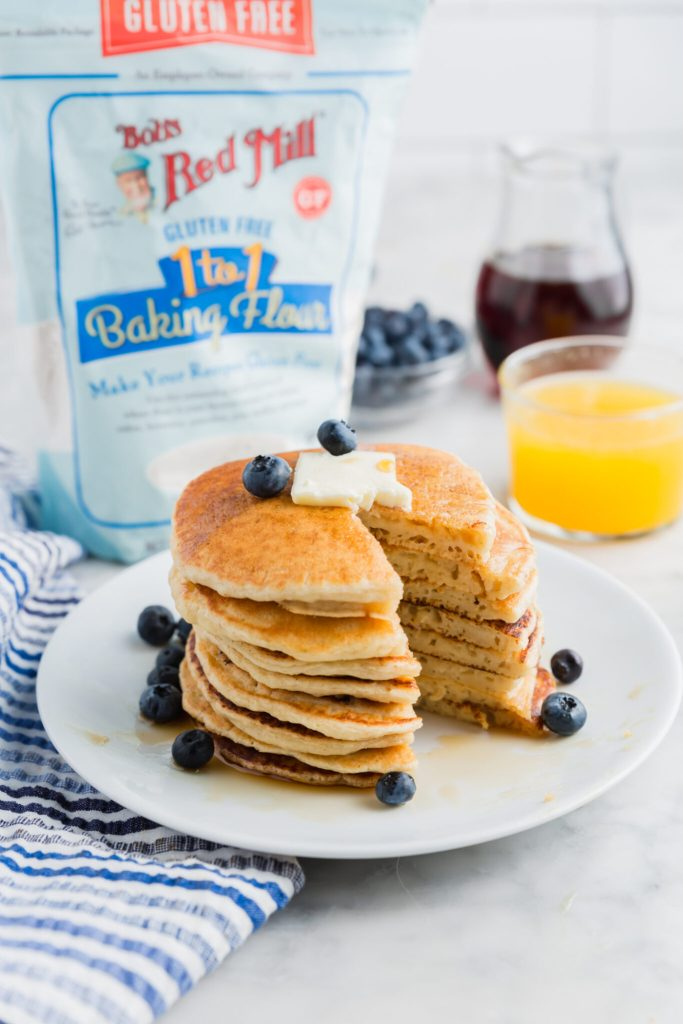 Stack of pancakes with a bite taken out of em and the Bob's Red Mill 1:1 gluten-free flour blend in the background and blueberries on top