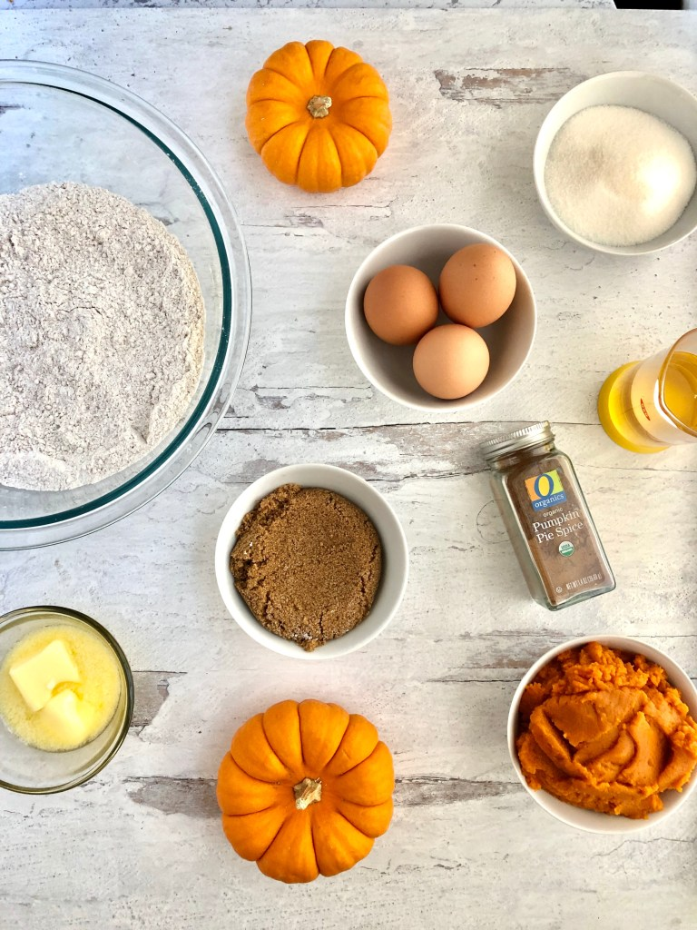 Ingredients for the pumpkin donuts including flour, pumpkin pie spice, brown sugar, butter, eggs and pumpkin puree.