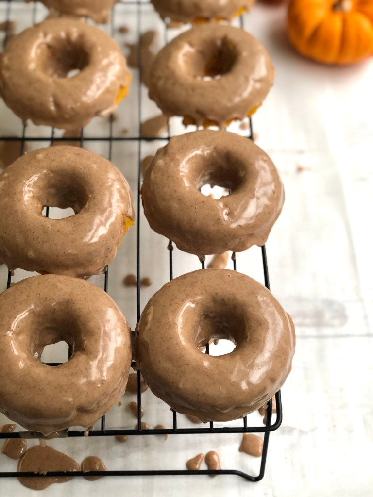 Up close on wet glazed pumpkin donuts