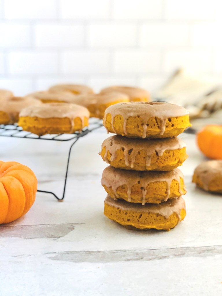 4 perfectly stacked pumpkin donuts with glaze dripping off of them.