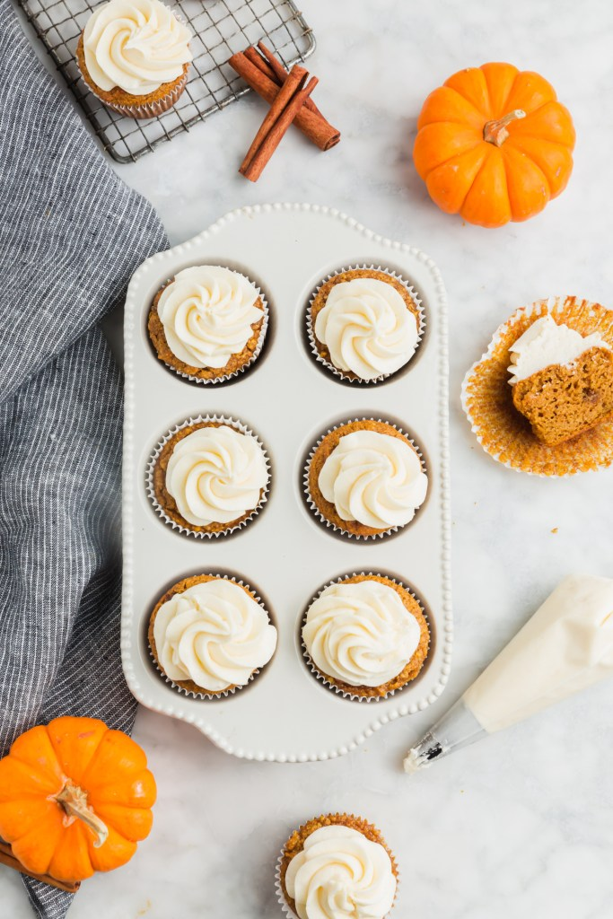 frosted almond flour pumpkin muffins in muffin pan