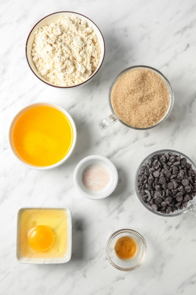 Picture of ingredients for gluten-free blondies including butter, chocolate chips, sugar, egg and vanilla.