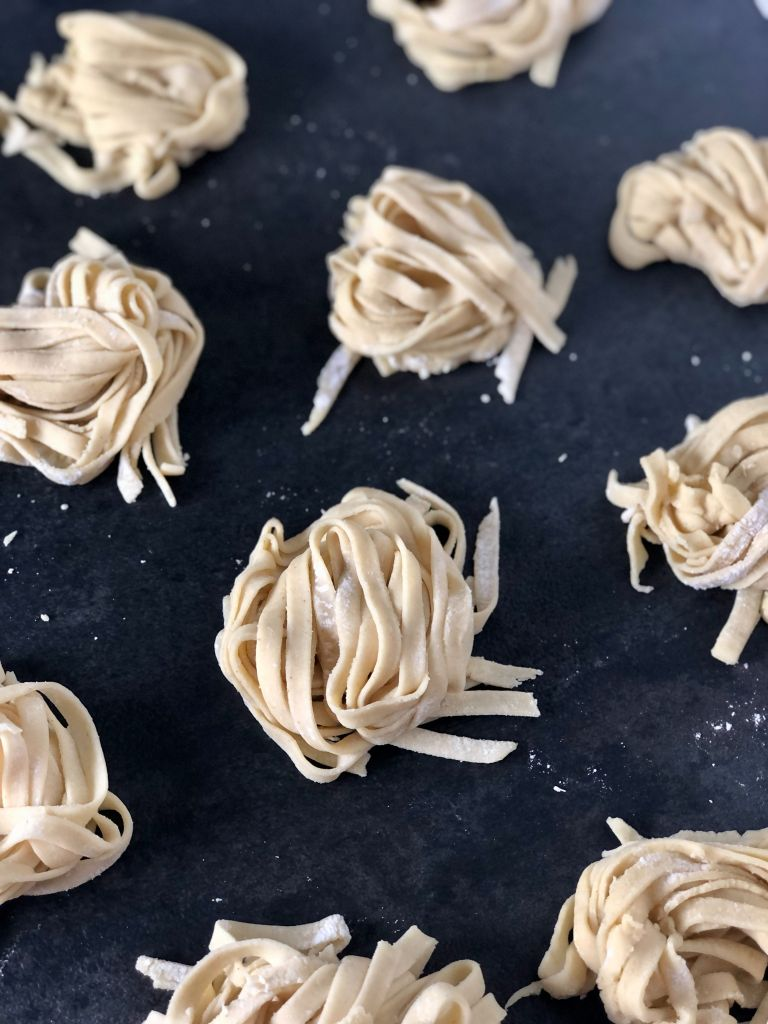 Picture of two ingredient gluten-free pasta cut into linguine noodles and on a black tray