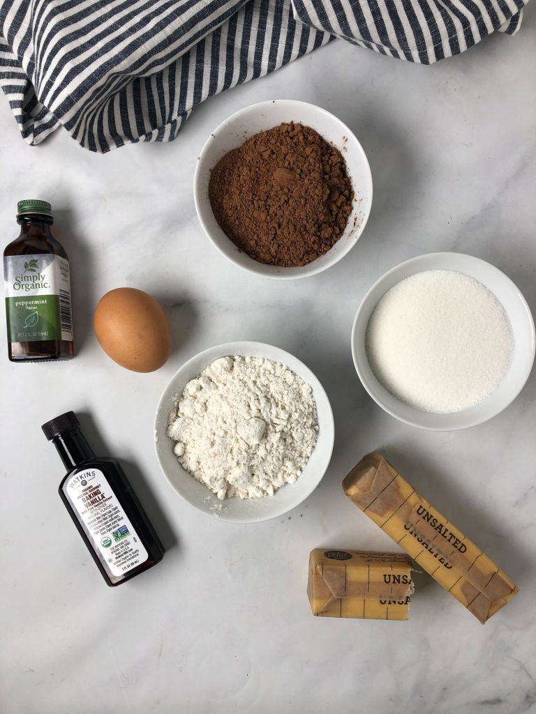 Picture of ingredients needed to make Thin Mint cookies - flour, cocoa, sugar, vanilla, peppermint extract, egg and butter