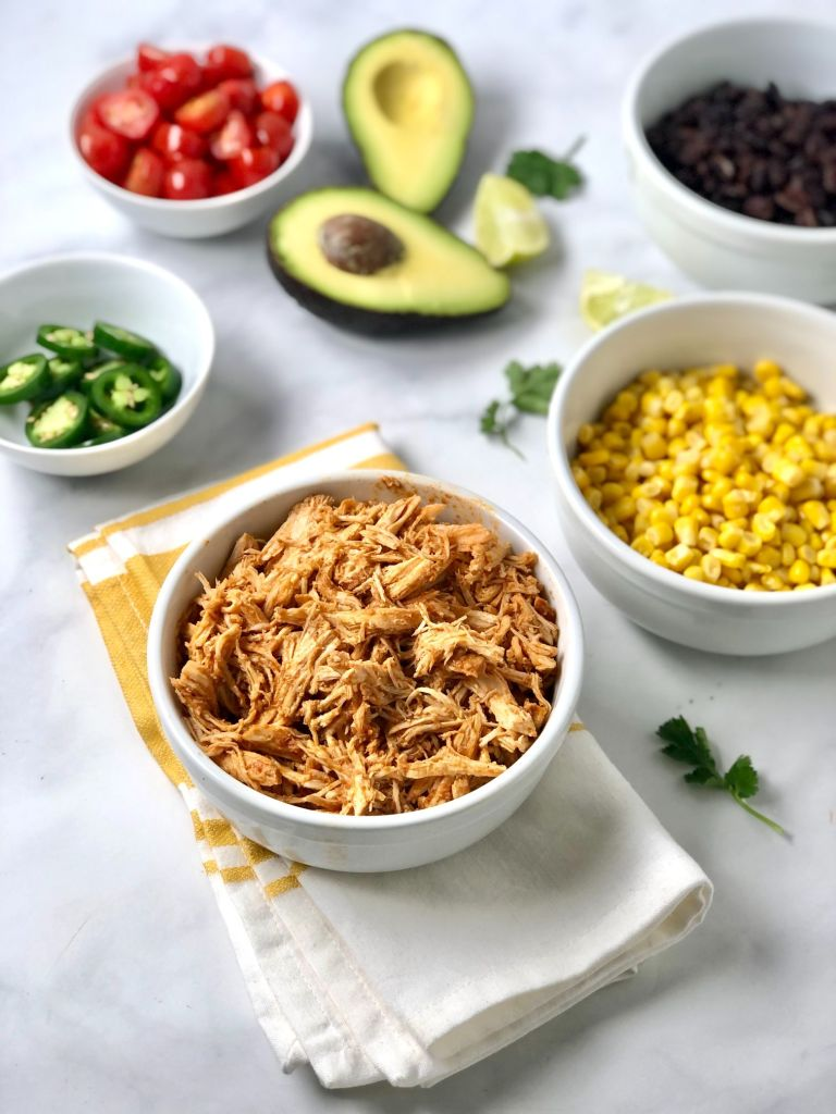 Picture of shredded chicken and other ingredients needed for the fresh chicken enchilada bowls