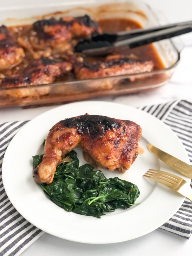 Baked BBQ Coke Chicken on a plate with spinach