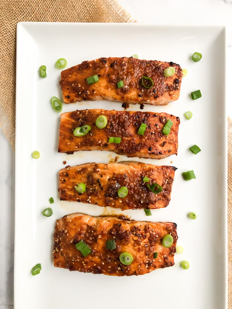 Cooked Asian salmon on a platter with green onions