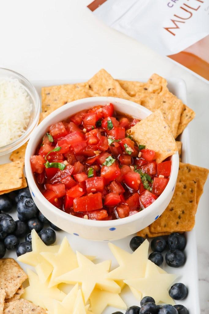 gluten-free bruschetta ingredients assembled and on a snack board
