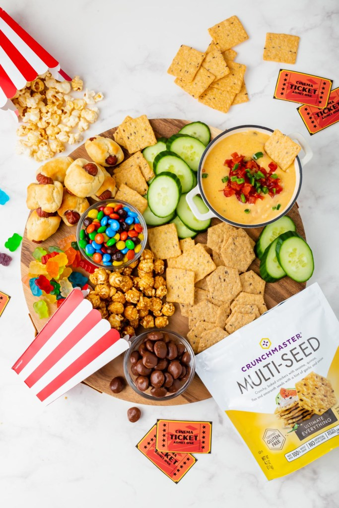 movie night-themed snack board overhead picture of queso, crackers, and sweet treats.
