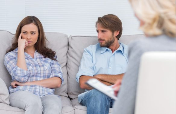 Troubled couple sit with arms folded in the office of the therapist