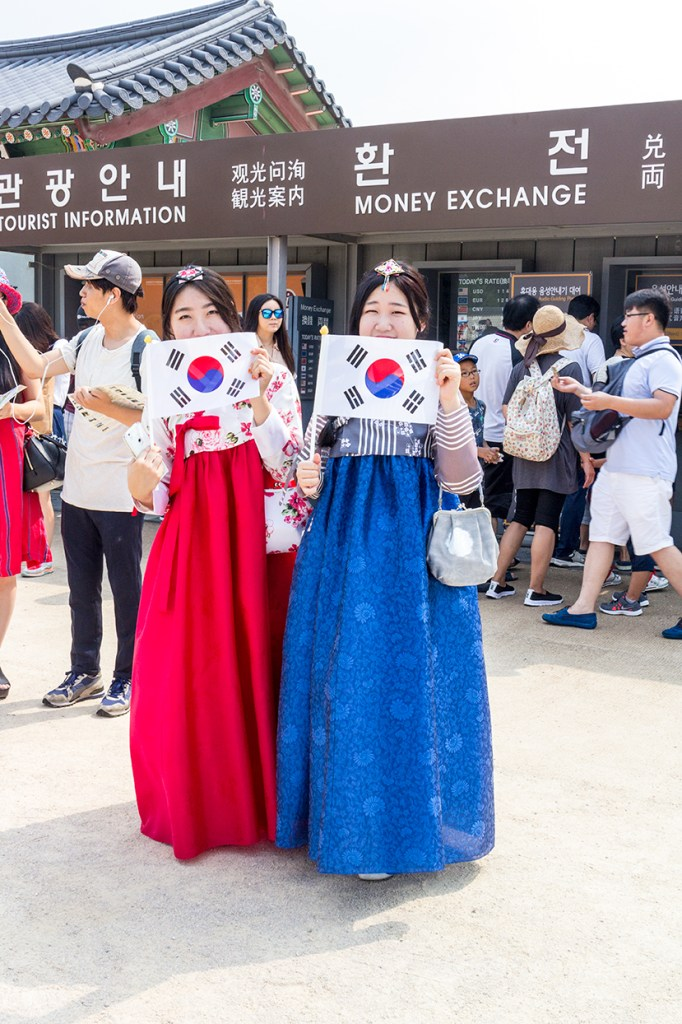Korean Women dressed in hanboks and holding the South Korean flag at Gyeongbokgung Palace